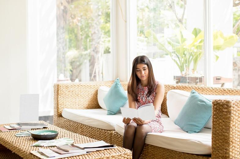 foto de mulher sentada no sofá olhando papel
